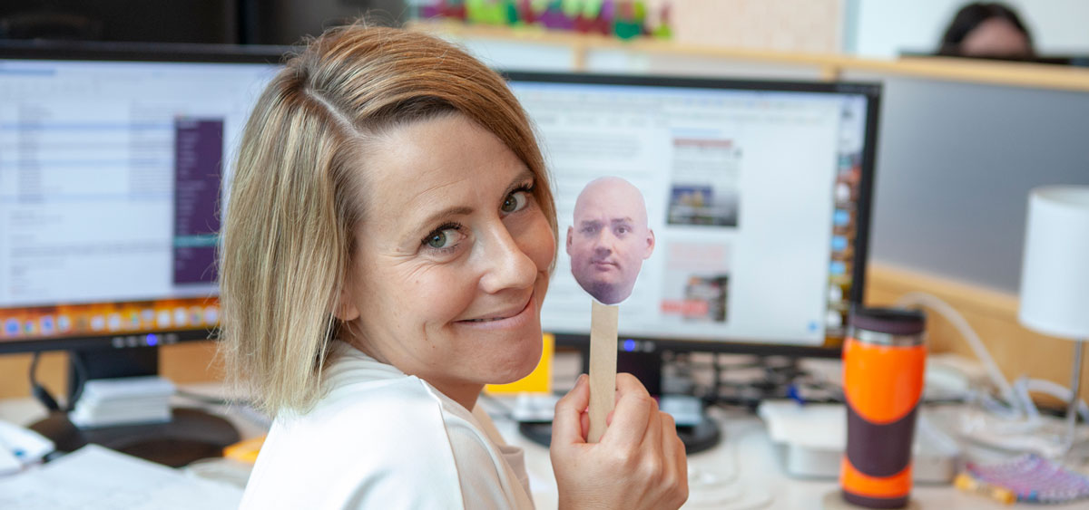 A photo of Erin holding up an image of Charlie's head on a popscicle stick